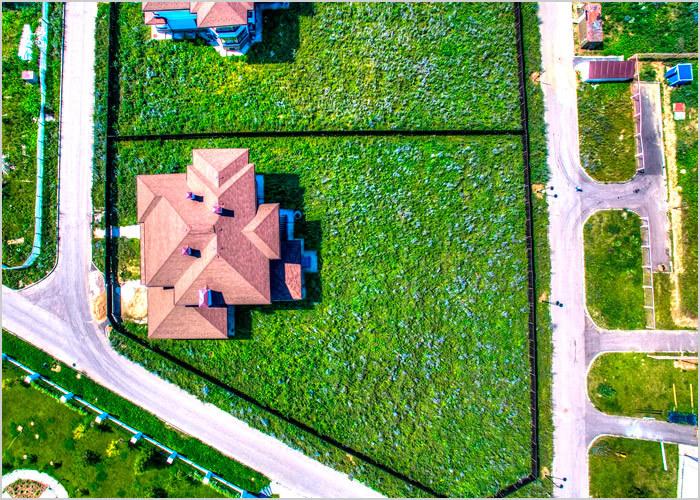 На фотографии представлен вид дачного участка, расположенного в коттеджном поселке, фото сделано с высоты птичьего полета при помощи квадрокоптера.